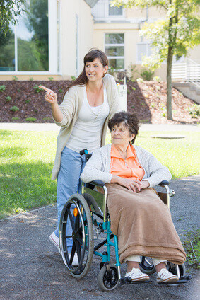 junge Pflegerin fhrt mit Seniorin spazieren im Rollstuhl